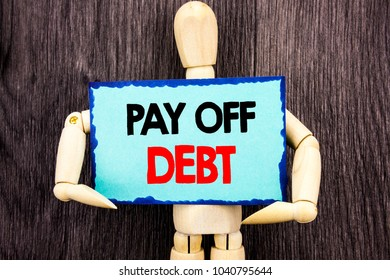 Writing text showing  Pay Off Debt. Concept meaning Reminder To Paying Owed Financial Credit Loan Bills written Sticky Note Holding By Sculpture the wooden background.
