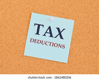 Writing text showing Tax Deductions. Business concept for Finance Incoming Tax Money Deduction written sticky note paper over a kork board.