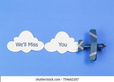 Writing of 'We'll Miss You' by a toy airplane with cloud on blue background