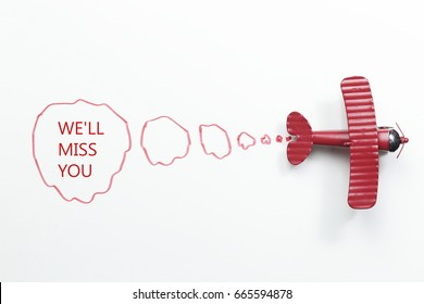 writing We'll Miss You red toy airplane with talk bubble on white background