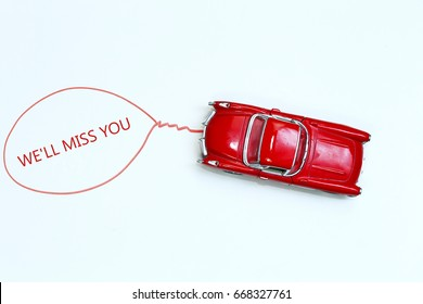 writing We'll Miss You red toy car with talk bubble on white background