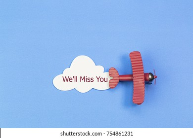 writing We'll Miss You red toy airplane with cloud on blue background