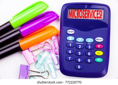 Writing word Microservices text in the office with surroundings such as marker, pen writing on calculator. Business concept for Micro Services white background with copy space