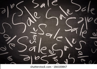 writing the word Sale on chalk board