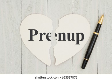 Writing up your prenuptial agreement, Heart-shape card on weathered wood background with text Prenup on each piece of the card