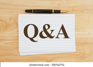 Writing your questions and answers, Stack of white index cards on wood desk with a pen with text Q&A