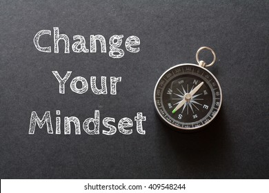Written Change Your Mindset words on black background with compass