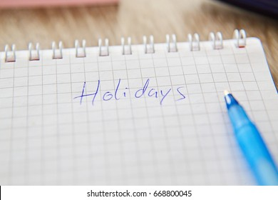 """Written """"Holidays"""" on notebook paper and pen"""