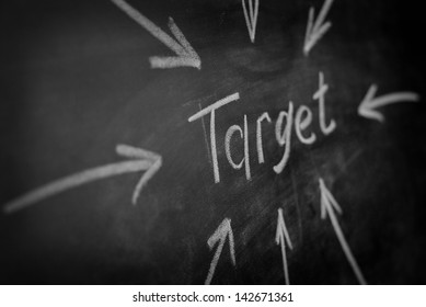 written on the blackboard the word target and an arrow