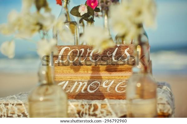 It is written on the label the word love flowers ocean water bottle wedding happiness romance