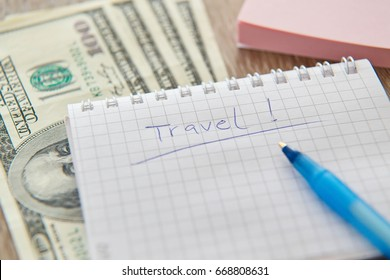 """Written """"TRAVEL"""" on notebook paper, dollars and pen"""