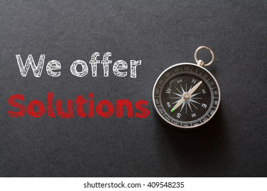 Written We Offer Solutions words on black background with compass