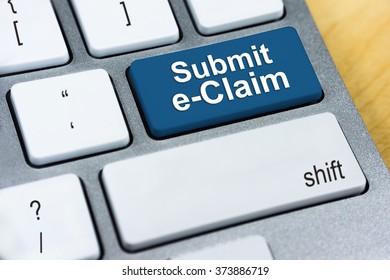 Written word Submit e-Claim on blue keyboard button. Online Tax Concept