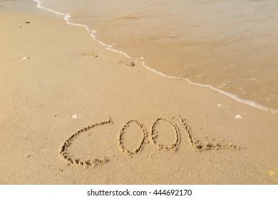 "written words ""COOL"" on sand of beach"
