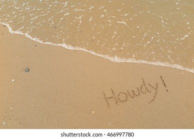 "written words ""Howdy !"" on sand of beach"