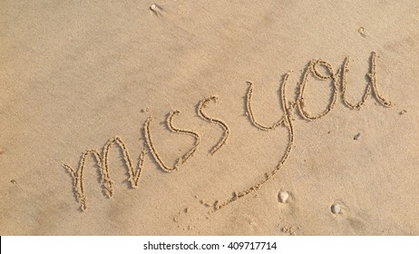 """written words """"miss you"""" on sand of beach"""