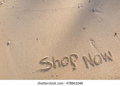 "written words ""Shop Now"" on sand of beach"