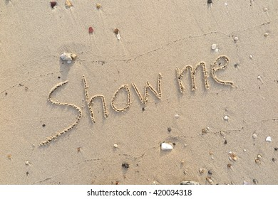 """written words """"Show me"""" on sand of beach"""