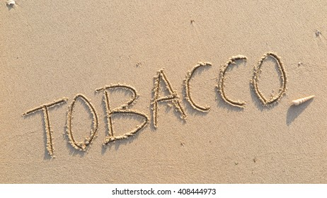 "written words ""TOBACCO"" on sand of beach"