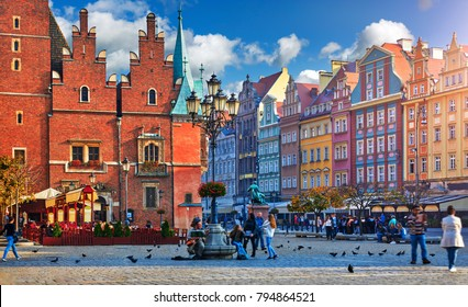 Wroclaw central market square with old colourful houses, street lamp and walking tourists people at evening sunset sunshine.