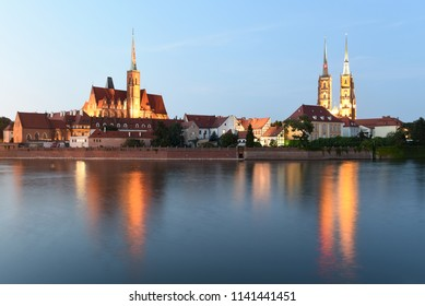 Wroclaw cityscape with Church of the Holy Cross and St. Bartholomew and Cathedral of St John the Baptist with river Odra at night, Wroclaw, Poland