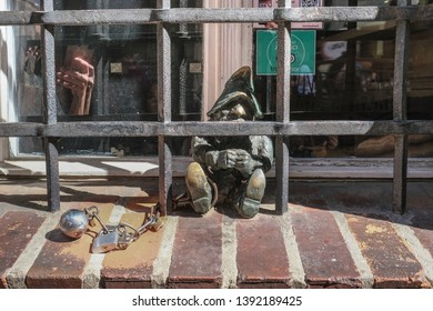Wroclaw, Lower Silesia, Poland - April 21, 2019: A Wroclaw dwarf sits  handcuffed behind the bars, outside the former city prison on Wiezienna street in Old Town Wroclaw