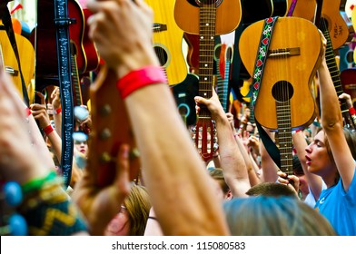 """WROCLAW - MAY 1: A crowd of people plays guitars in a Wroclaw market square at the """"Annual Thanks Jimi Guitar Festival"""" in order to beat the Guinness Record on May 1, 2012 in Wroclaw, Poland."""