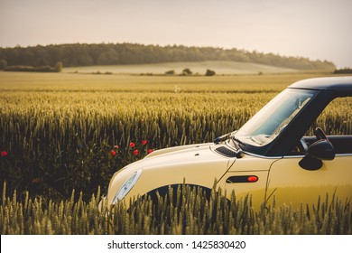 Wroclaw, Poland - 11 June 2019 - Yellow Mini Cooper R50 on countryside road between wheat fields in sunset time.