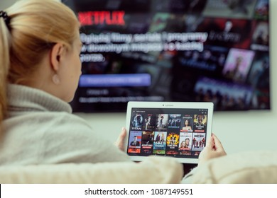 WROCLAW, POLAND - APRIL 03rd, 2018: Woman is using Netflix application on her tablet. Netflix is an american entertainment company specialized in streaming media.