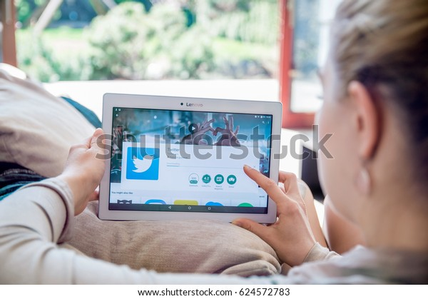 WROCLAW, POLAND- APRIL 10th, 2017:  Woman is installing Twitter application on Lenovo tablet. Twitter  is an online news and social networking service where users post and interact with messages