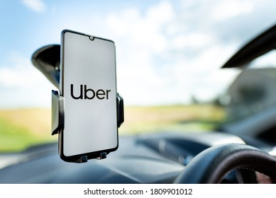 Wroclaw, Poland - AUG 25, 2020: Uber driver holding smartphone in car. Uber is sharing-economy service for ubran transport.
