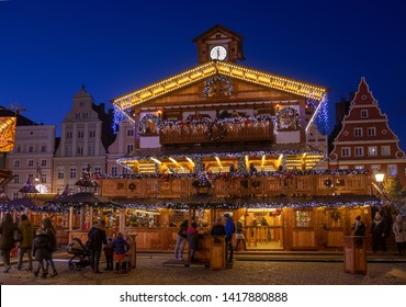 WROCLAW, POLAND - DECEMBER 12, 2019: Beautiful illuminated wooden pavilion at traditional Christmas market at Wroclaw. Night time. Poland