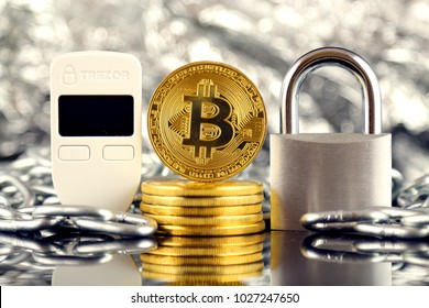 WROCLAW, POLAND - FEBRUARY 17, 2018: Physical version of Bitcoin, Trezor (cryptocurrency hardware wallet), silver padlock and chain. Studio shot.