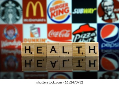 WROCLAW, POLAND - FEBRUARY 19, 2020: Word HEALTH made of wooden letters, and STARBUCKS, McDONALDS, BURGER KING, SUBWAY, KFC, WENDY'S, DUNKIN DONUTS, COCA COLA, PIZZA HUT, PEPSI logos in background