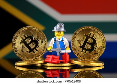 WROCLAW, POLAND - JANUARY 07, 2018: Physical version of Bitcoin, miner (as Lego figure) and South Africa Flag. Studio shot.