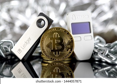 WROCLAW, POLAND - JULY 06, 2019: Physical version of Bitcoin (BTC), Trezor and Ledger (cryptocurrency hardware wallets), and chain (like Blockchain Technology). Studio shot.