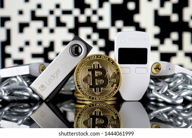 WROCLAW, POLAND - JULY 06, 2019: Physical version of Bitcoin (BTC), Trezor and Ledger (cryptocurrency hardware wallets), silver padlocks and chain (like Blockchain Technology). Studio shot.