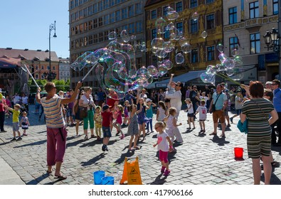 WROCLAW, POLAND - JUNE 03, 2015: Kids play with soap bubble.