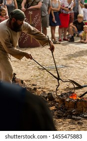"""WROCLAW POLAND - JUNE 16 2019: """"People of Fire"""" (Pol: """"Ludzie Ognia"""") event. Educational show about archaic and traditional crafts concern fire. People smelt steel in a clay furnace"""