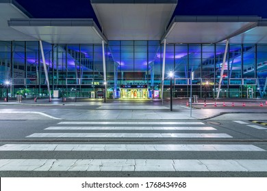 Wroclaw, Poland - June 17, 2020: Zebra crossing in front of modern building of Wroclaw Airport terminal at dusk. Entrance to arrivals hall thorough street. Airport at night