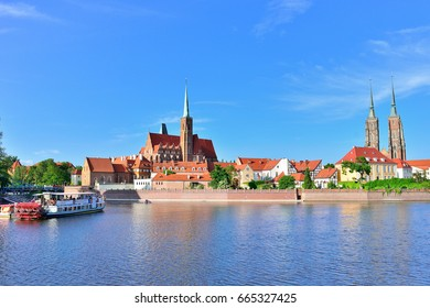 WROCLAW, POLAND - JUNE, 2017: View on Church of the Holy Cross and St. Bartholomew, Odra river and Tumski Island, Wroclaw, Poland. A popular tourist place.