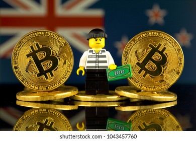 WROCLAW, POLAND - MARCH 10, 2018: Physical version of Bitcoin, Robber (as Lego figure) and New Zealand Flag. Studio shot.