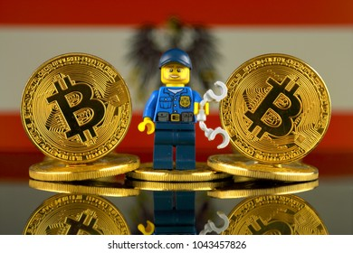WROCLAW, POLAND - MARCH 10, 2018: Physical version of Bitcoin, Police Officer (as Lego figure) and Austria Flag. Studio shot.