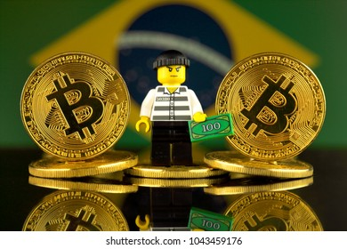 WROCLAW, POLAND - MARCH 10, 2018: Physical version of Bitcoin, Robber (as Lego figure) and Brazil Flag. Studio shot.