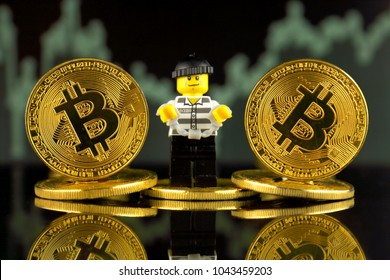 WROCLAW, POLAND - MARCH 10, 2018: Physical version of Bitcoin and Robber (as Lego figure). Studio shot.