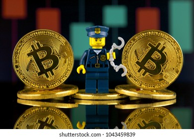 WROCLAW, POLAND - MARCH 10, 2018: Physical version of Bitcoin and Police Officer (as Lego figure). Studio shot.