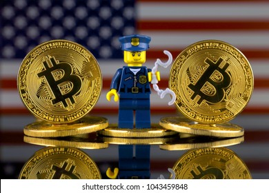 WROCLAW, POLAND - MARCH 10, 2018: Physical version of Bitcoin, Police Officer (as Lego figure) and United States Flag. Studio shot.