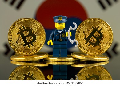 WROCLAW, POLAND - MARCH 10, 2018: Physical version of Bitcoin, Police Officer (as Lego figure) and South Korea Flag. Studio shot.