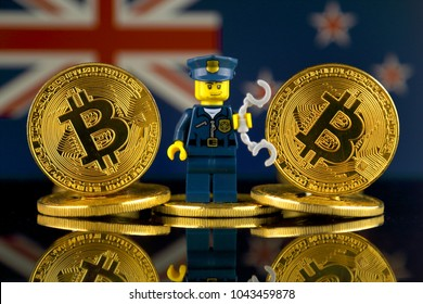 WROCLAW, POLAND - MARCH 10, 2018: Physical version of Bitcoin, Police Officer (as Lego figure) and New Zealand Flag. Studio shot.