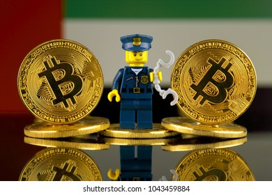 WROCLAW, POLAND - MARCH 10, 2018: Physical version of Bitcoin, Police Officer (as Lego figure) and United Arab Emirates Flag. Studio shot.